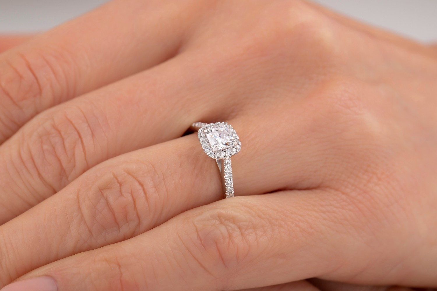 Art Deco Style Ring/Diamond Cluster Engagement Ring for Women in platinum with a cushion cut centre stone surrounded by small round brilliant cut diamonds all in a claw setting-img1